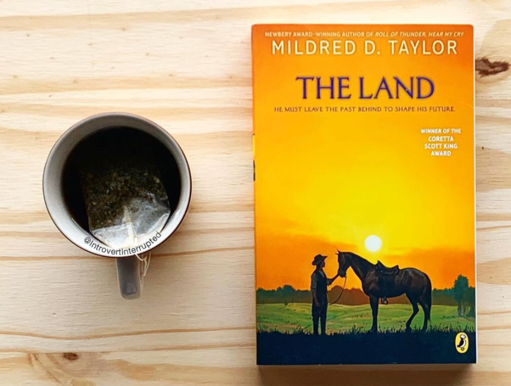 "A copy of ""The Land"" by Mildred D. Taylor next to a cup of tea on a wooden surface with an @IntrovertInterrupted watermark on the cup."